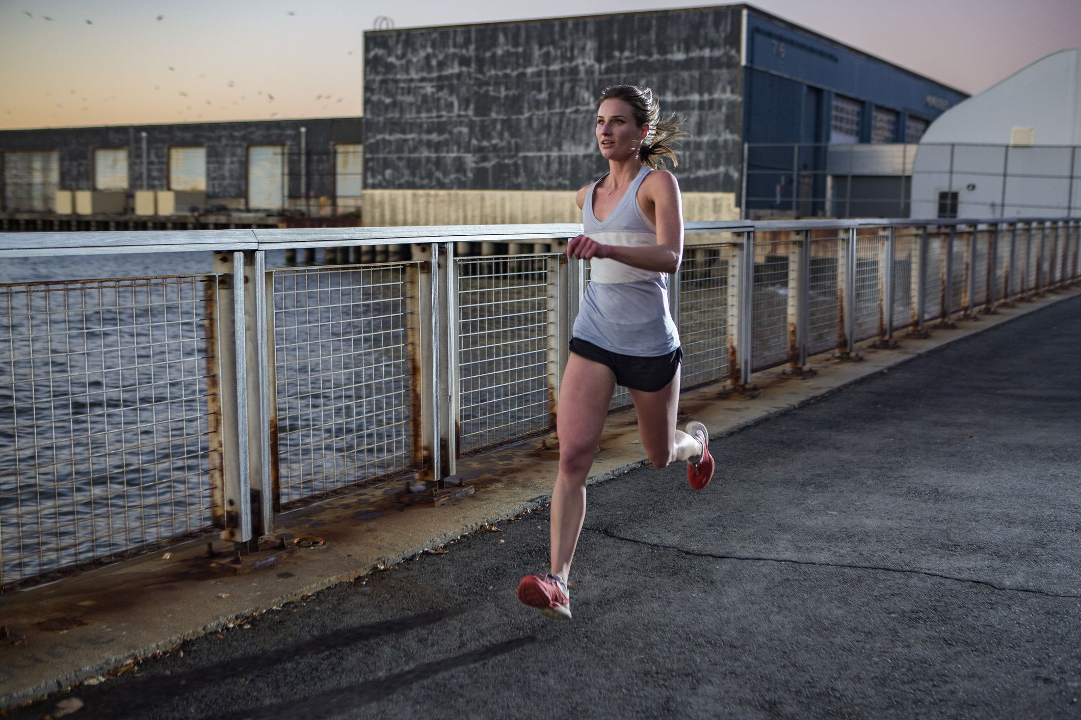 female-running-along-waterfront-at-twilight-high-res-stock-photography-623477697-1562011819
