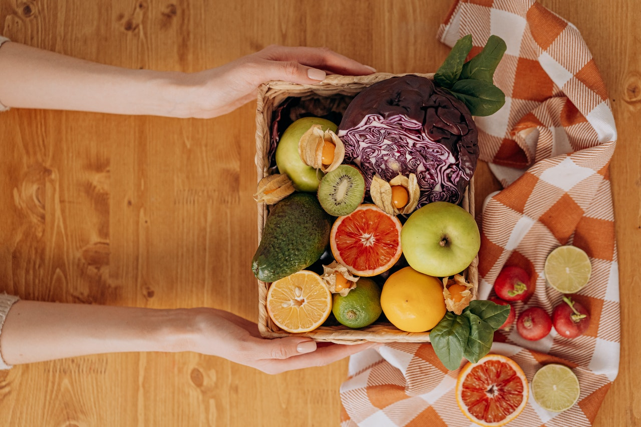 woman holding a basket full of autumn fruit